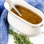 Brown gravy in a white gravy boat with thyme next to it