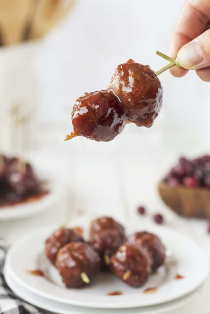 Close up shot of a hand holding cocktail meatballs on a toothpick over a plate full of them