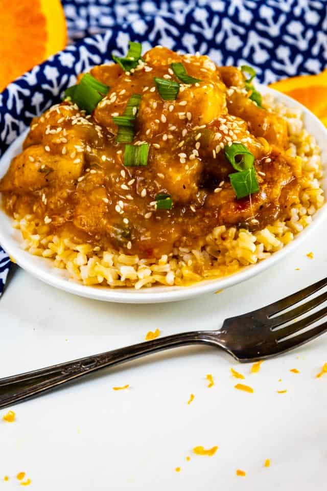 Overhead shot of orange chicken over rice in a white bowl with fork next to it