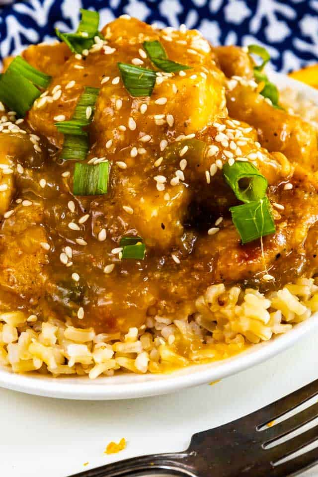 Close up shot of orange chicken served over rice in a white bowl