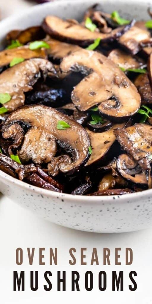 Close up shot of oven seared mushrooms in a serving bowl with recipe title on bottom of image