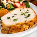 Close up shot of a slice of roasted turkey breast on a white plate with salad and a fork and recipe title on bottom of image
