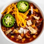 Overhead shot showing bowl of turkey chili with cheese, onions and jalapenos on top