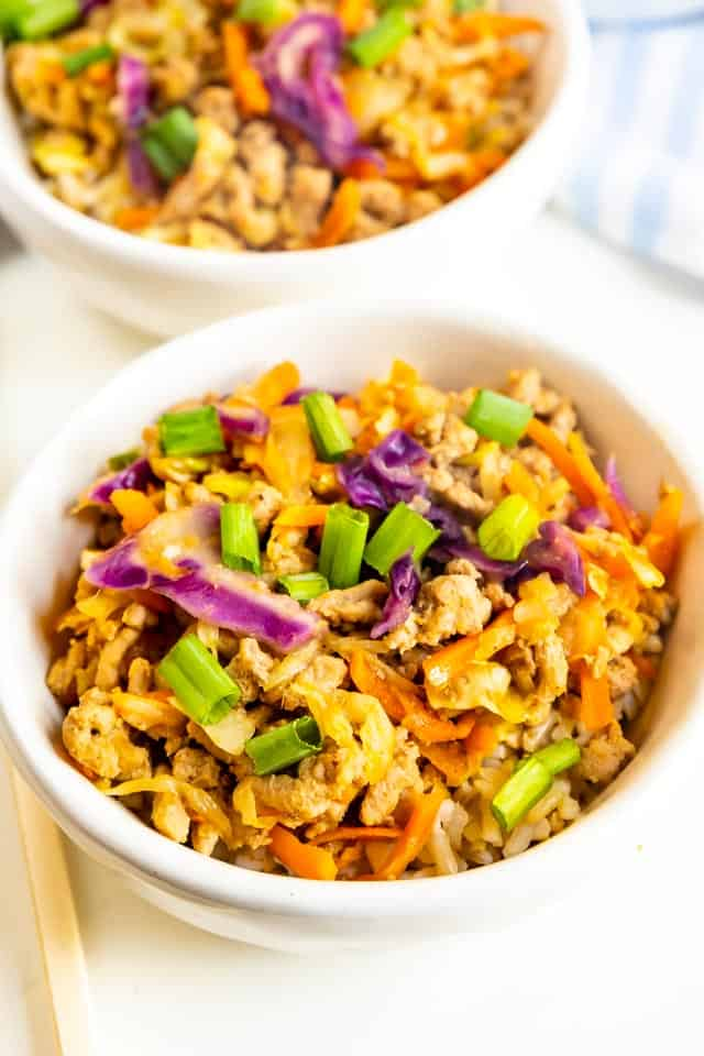 Close up shot of egg roll in a bowl with chopsticks and another bowl behind it