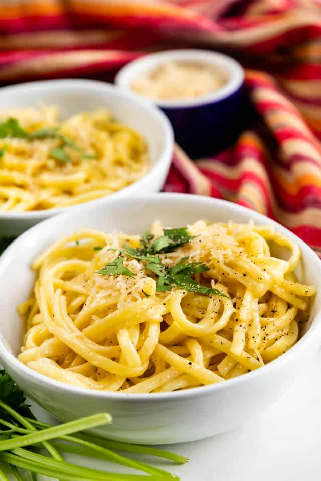 Two bowls of garlic butter pasta with red striped dish towel in background