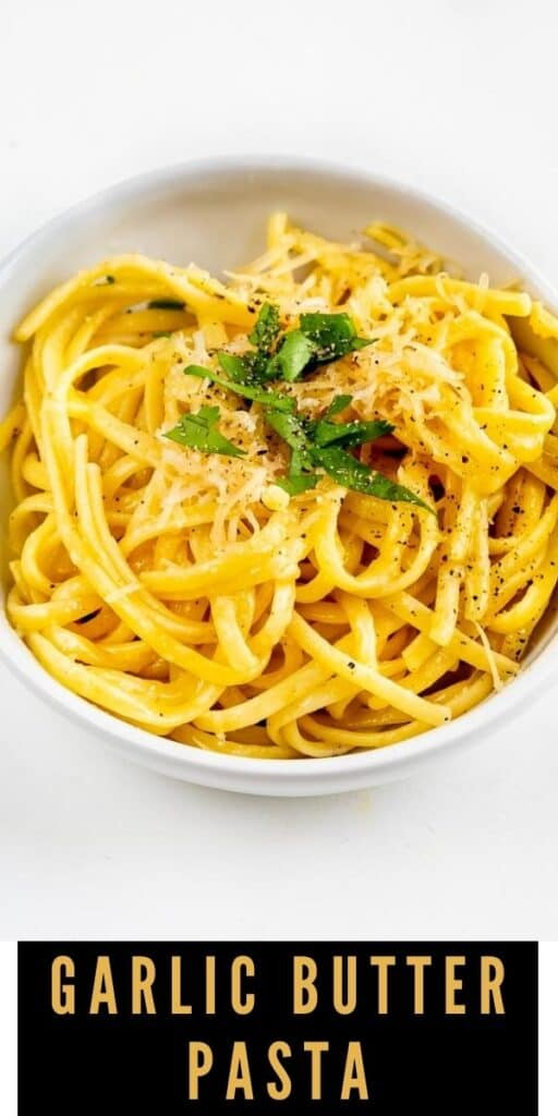 Overhead view of garlic butter pasta in a white bowl with recipe title on bottom of image