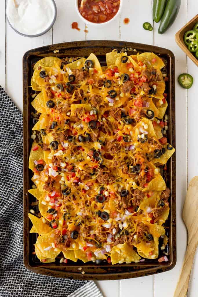 Overhead view of sheet pan nachos with all the toppings on top