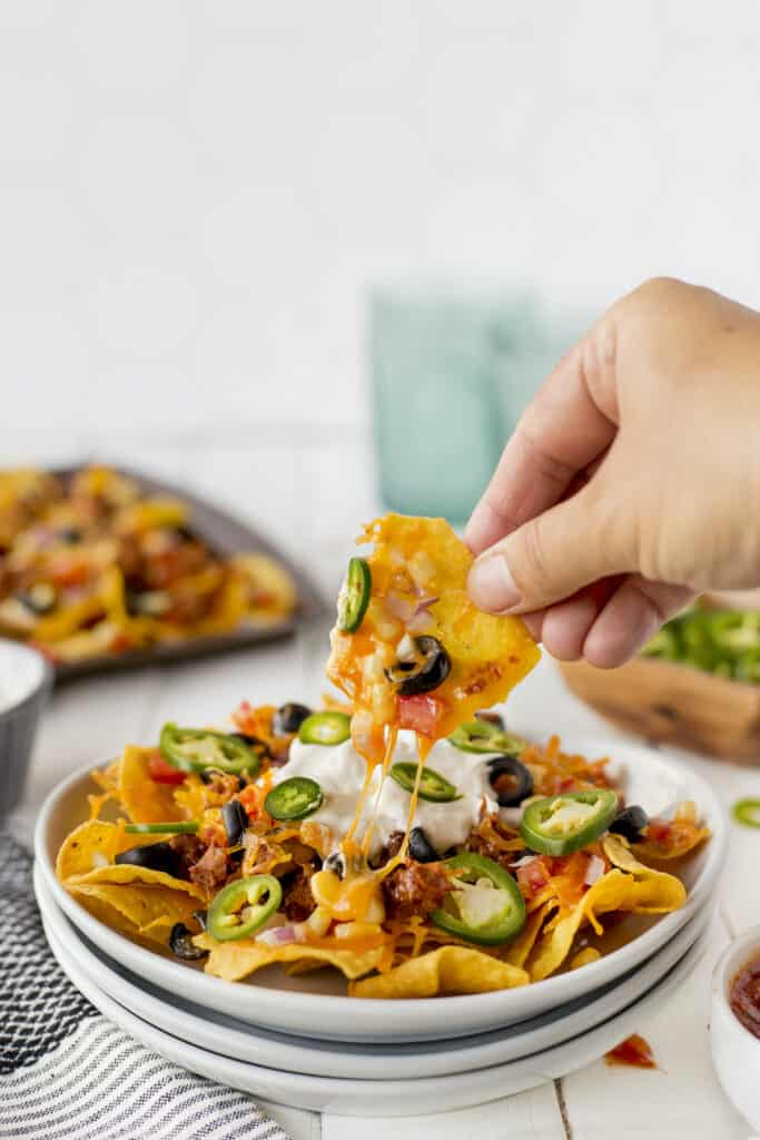 Plate full of vegetarian sheet pan nachos with hand pulling one off plate