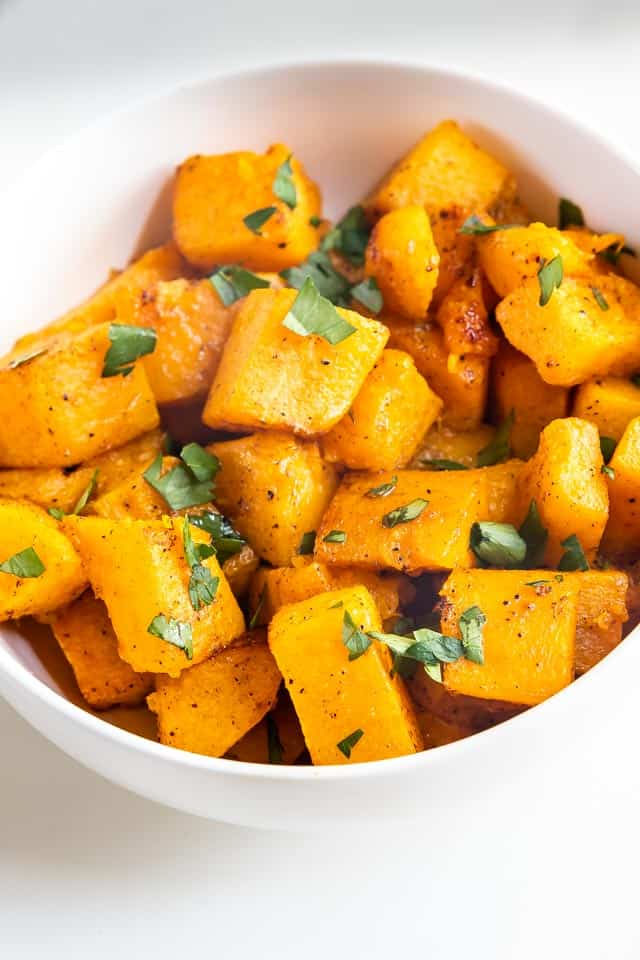 Overhead shot of cubed roasted butternut squash in a white bowl topped with herbs
