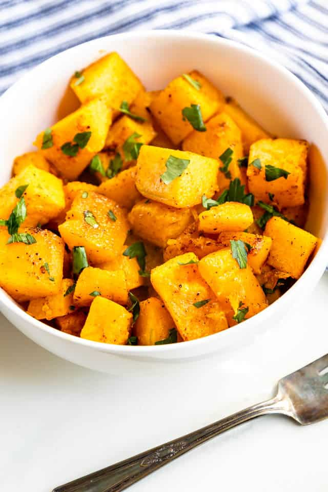 Roasted butternut squash cut into cubes and placed in a bowl topped with herbs