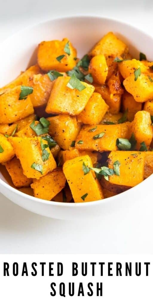Overhead shot of cubed roasted butternut squash in a white bowl topped with herbs and recipe title on bottom of photo