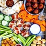 Overhead view of appetizer board filled with different appetizers and snacks