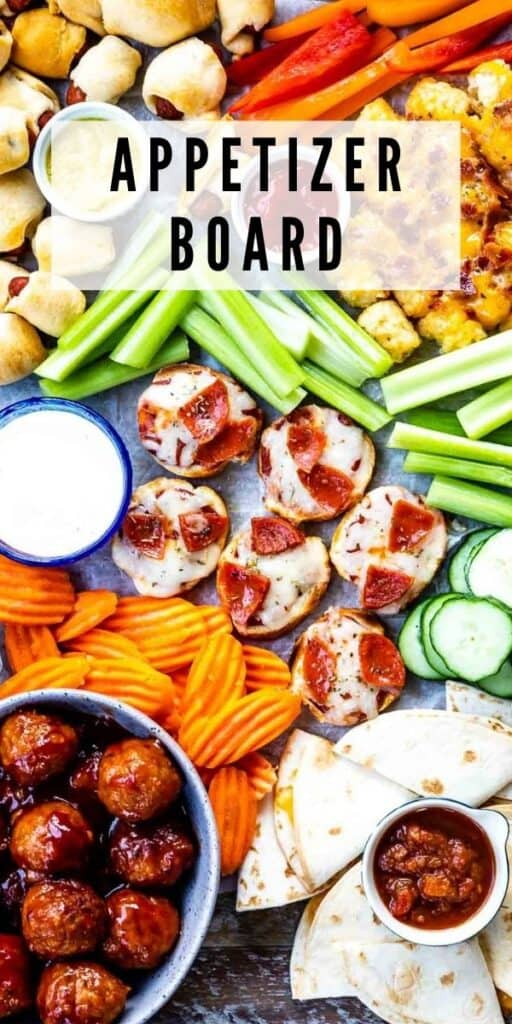 Overhead view of appetizer board filled with different appetizers and snacks with recipe title on image