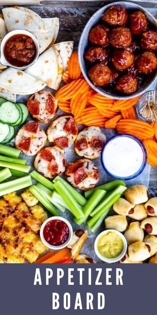 Overhead view of appetizer board filled with different appetizers and snacks with recipe title on bottom of image