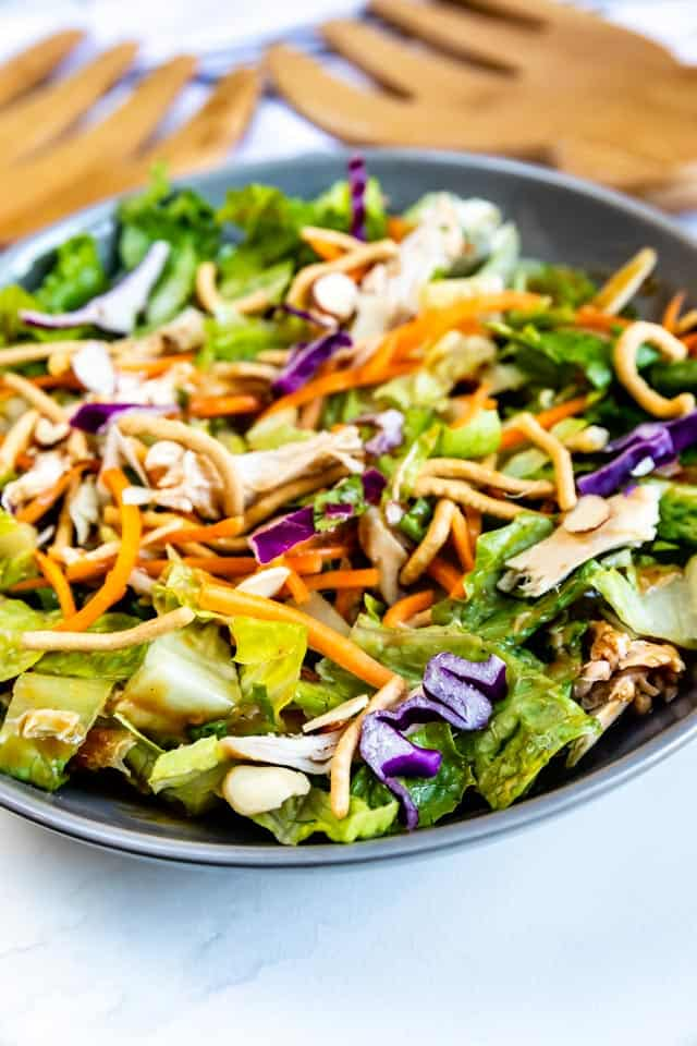 Bowl of chinese chicken salad with wooden serving forks in background and recipe title on bottom right of image