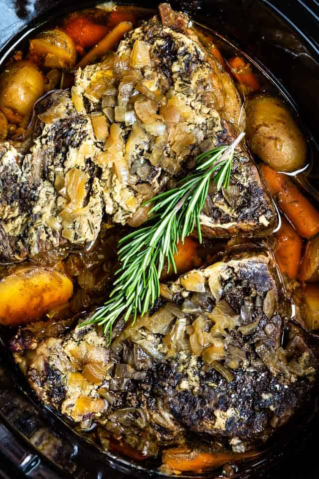 Overhead view of pot roast ingredients in black slow cooker