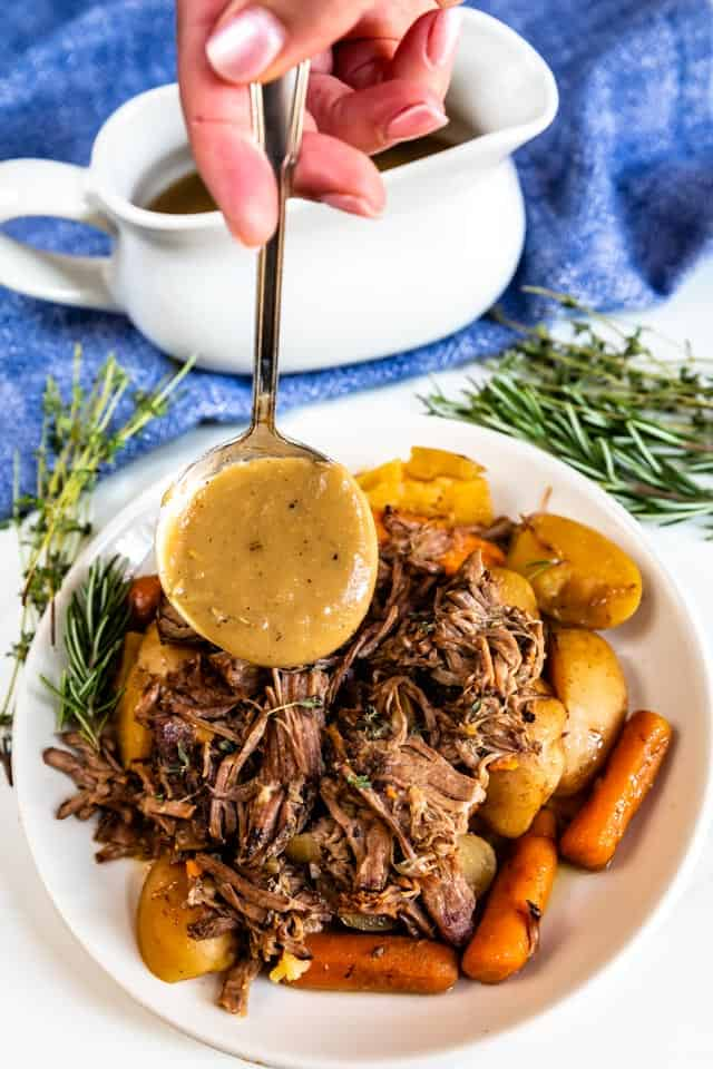 Gravy being poured over crockpot pot roast on a white plate