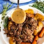 Gravy being poured over crockpot pot roast on a white plate with recipe title on bottom of image