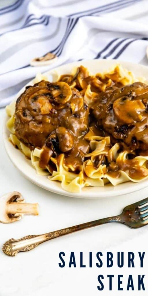 Salisbury steak on a plate over egg noodles with a fork and cloth napkin on table with recipe title on bottom right of image