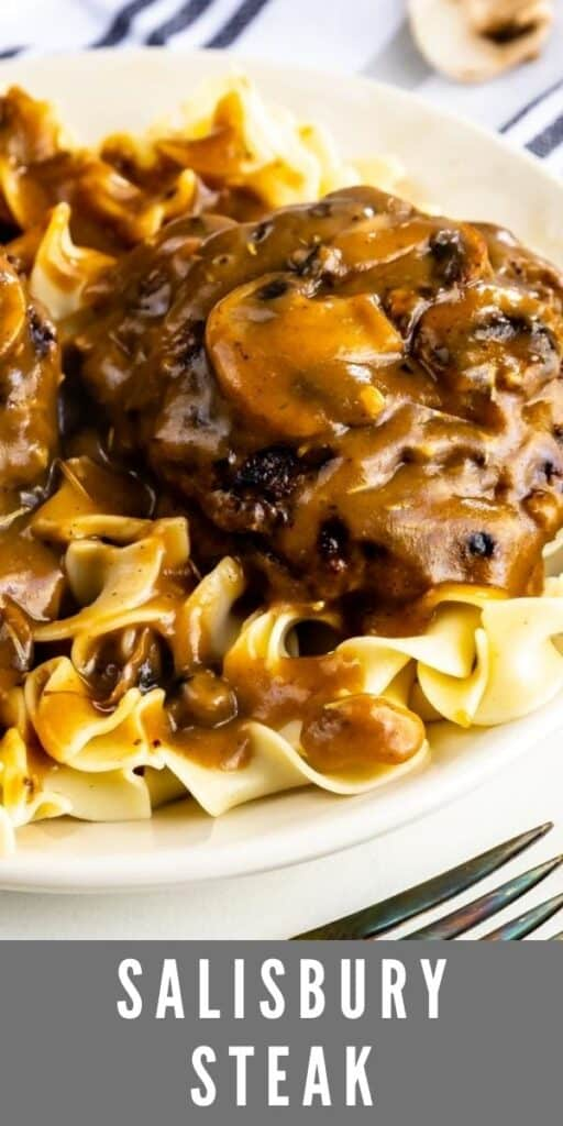 Close up photo of salisbury steak over egg noodles on a white plate with recipe title on bottom of image