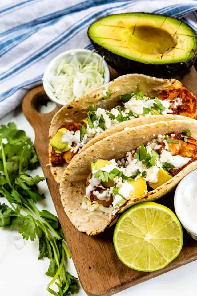 Two shrimp tacos on a wood cutting board with toppings around them