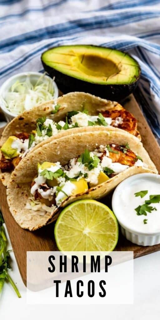 Two shrimp tacos on a wood cutting board with toppings around them and recipe title on bottom of image