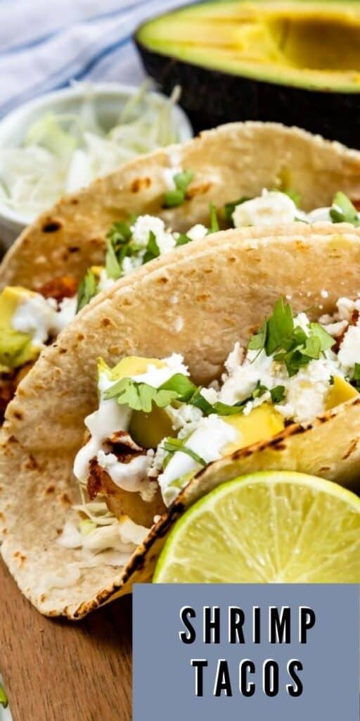 Close up shot of two shrimp tacos with an avocado and lime in the photo and recipe title in bottom right corner of photo