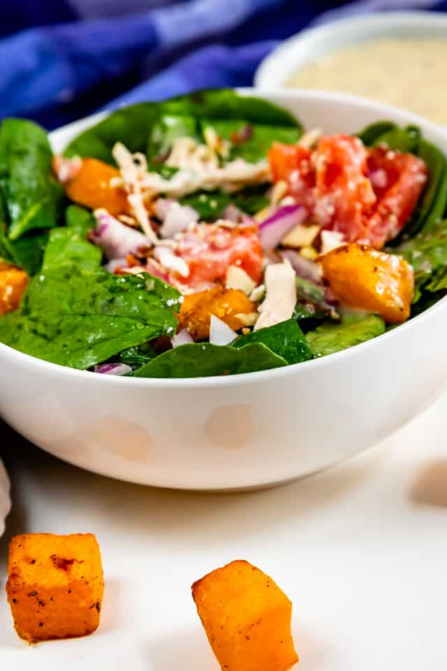 Side shot of spinach salad in a white salad bowl with butternut squash on the side