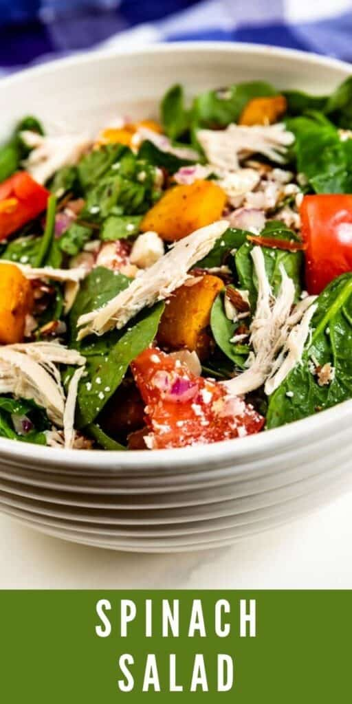 Spinach salad in a white salad bowl with recipe title on bottom of image
