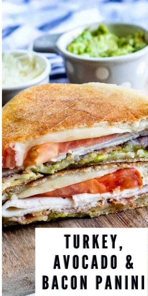 Turkey Avocado Bacon Panini cut in half and stacked on a wooden cutting board with recipe title in bottom right corner of image