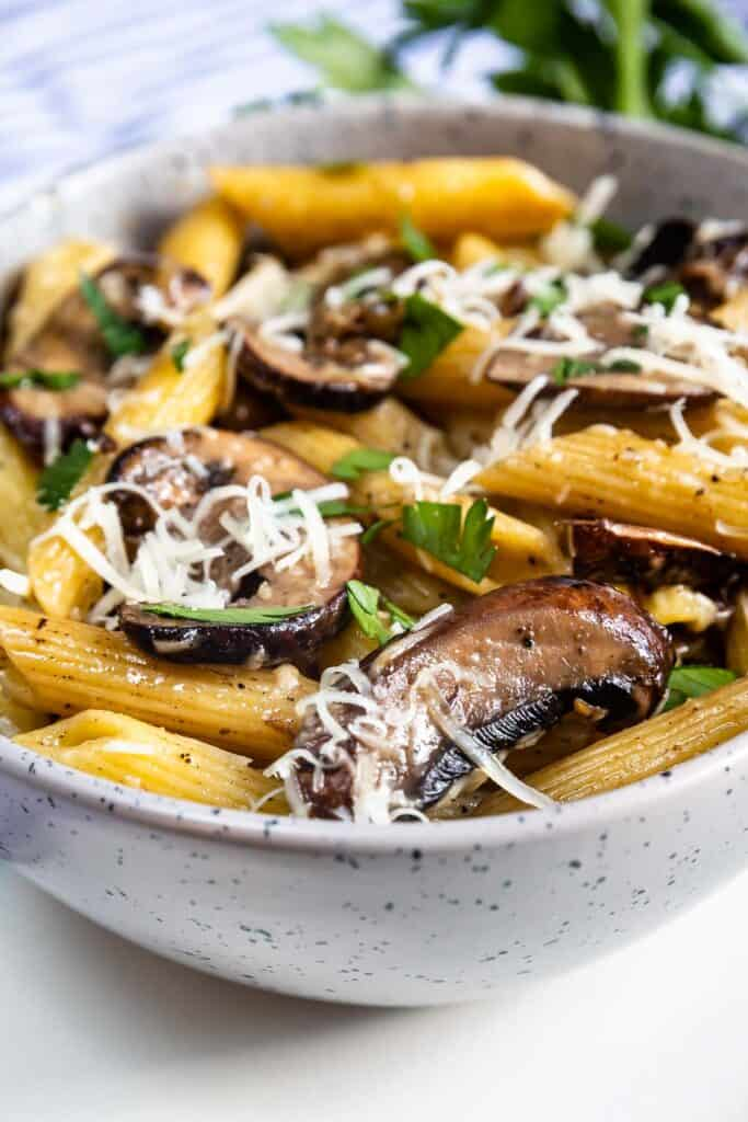 Close up side photo of mushroom pasta in a bowl with parmesan cheese on top