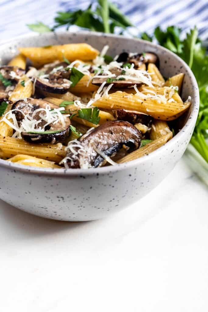 Mushroom pasta in a bowl with shaved parmesan cheese on top