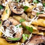Close up shot of mushroom penne pasta with parmesan cheese on top