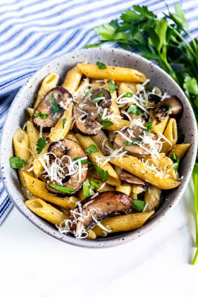 Overhead shot of mushroom pasta in a bowl with parsley next to it