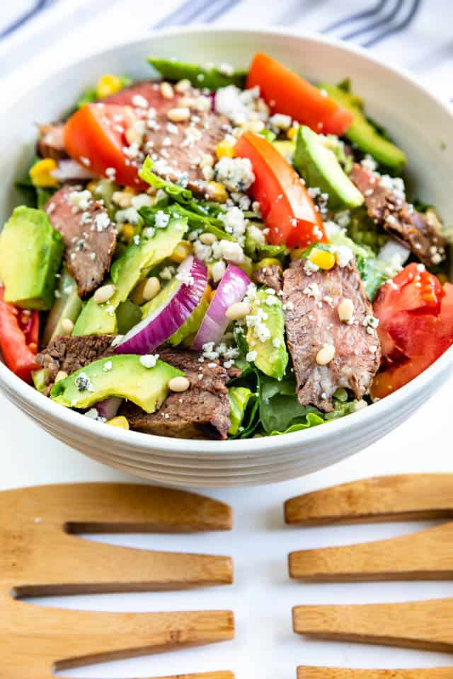 Steak salad in large bowl with wooden salad utensils in front of it