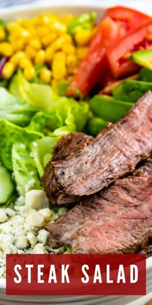 Close up shot of steak salad ingredients all in one bowl and recipe title on bottom of photo