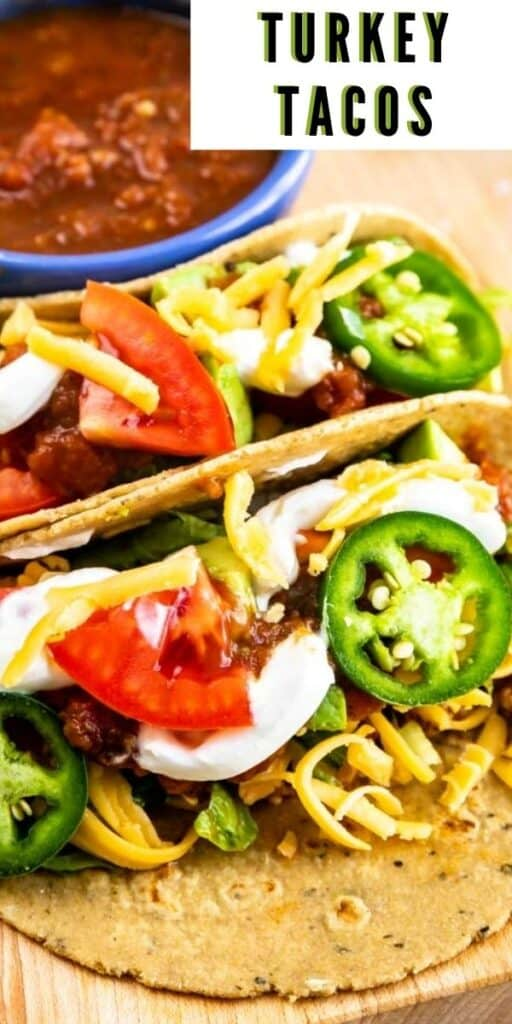 Close up shot of two turkey tacos with lots of taco toppings and recipe title in top right corner