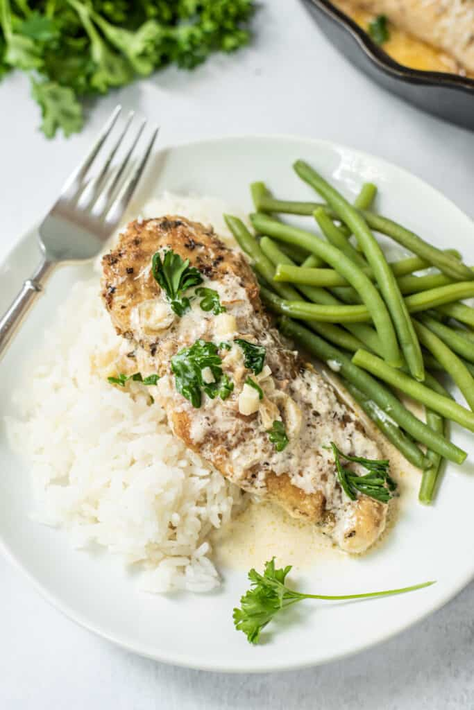 Chicken in garlic sauce plated with green beans and white rice
