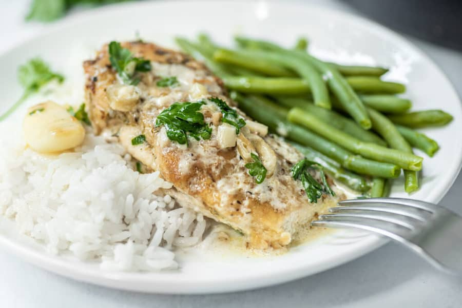 Close up side shot of chicken in garlic sauce plated with green beans and white rice