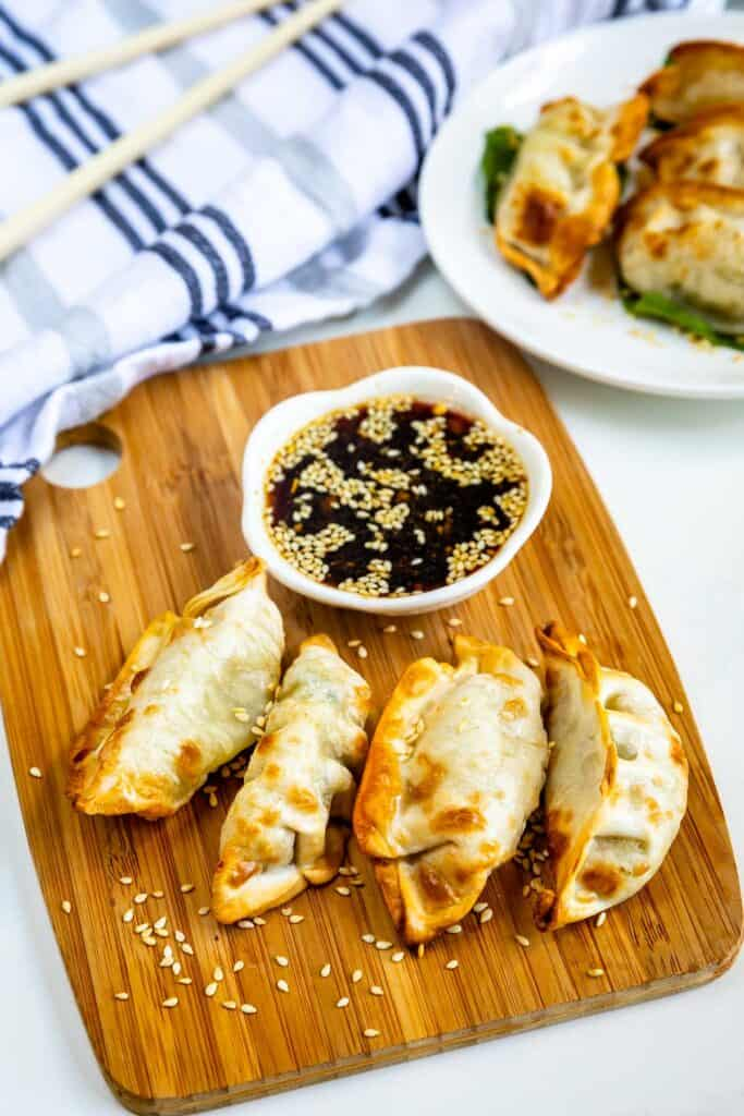 Overhead view of four potstickers on a wood cutting board with sauce next to them