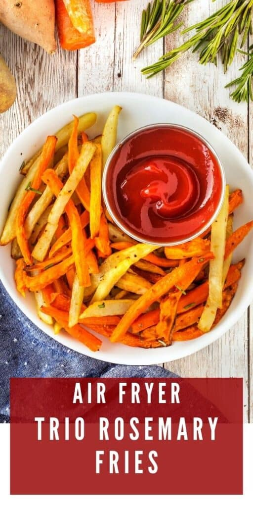 Overhead shot of air fryer fries with ketchup in a white bowl with recipe title on bottom of photo