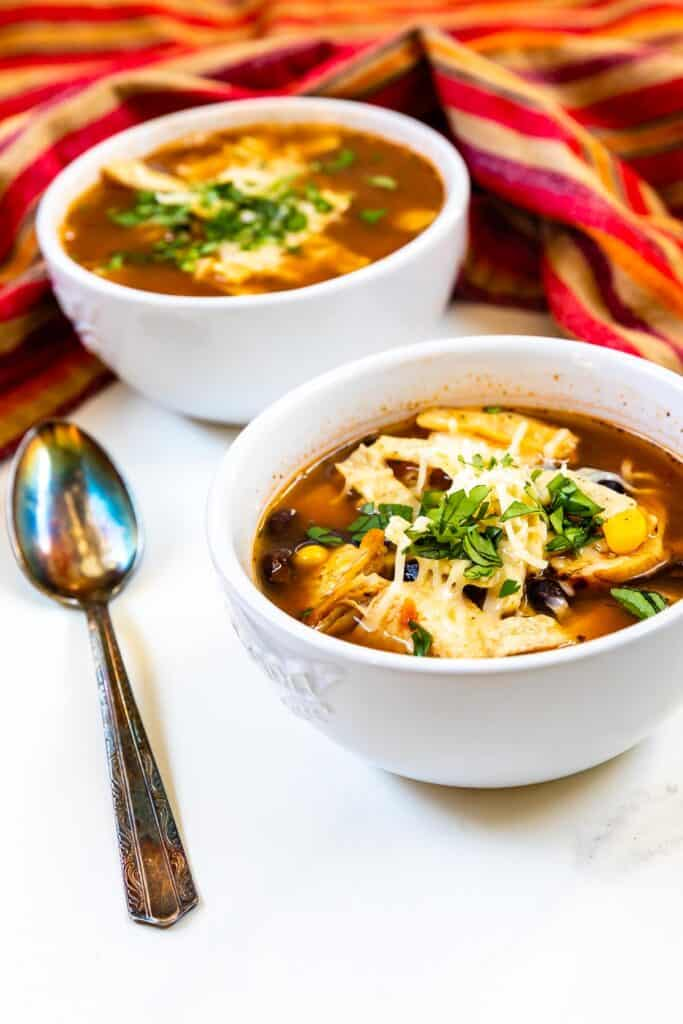 Two bowls of easy chicken tortilla soup with spoon next to bowl