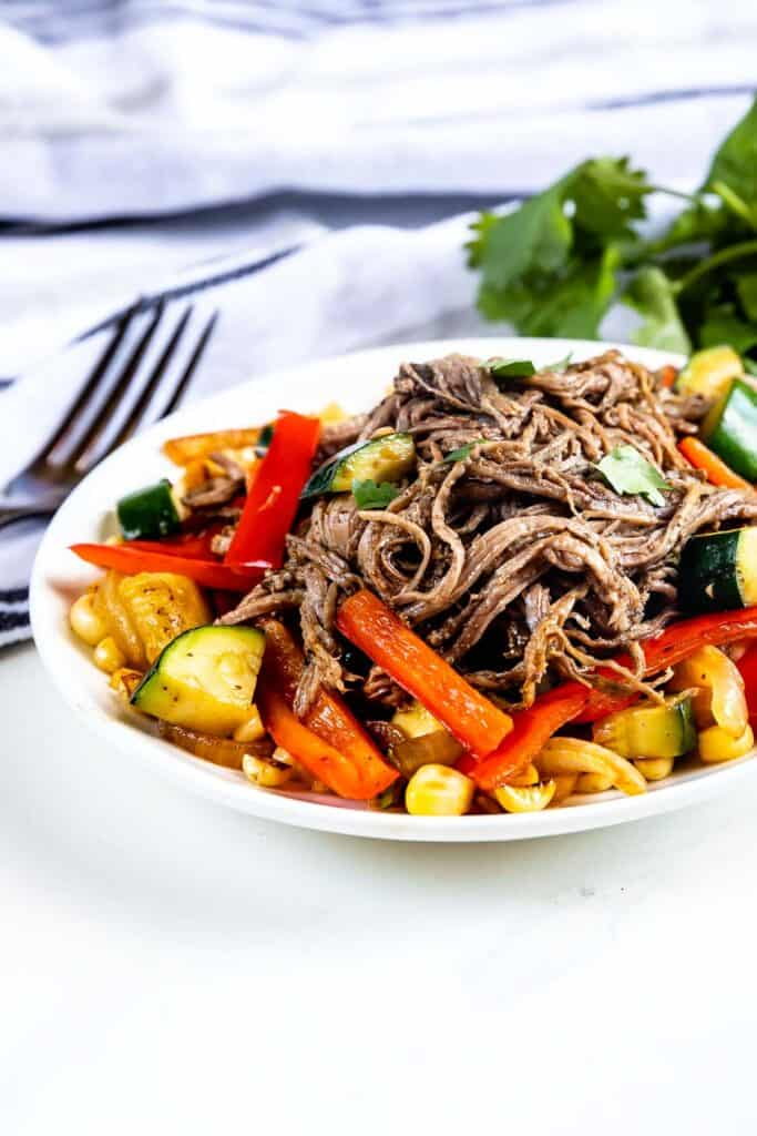 Crockpot flank steak on a plate with veggies