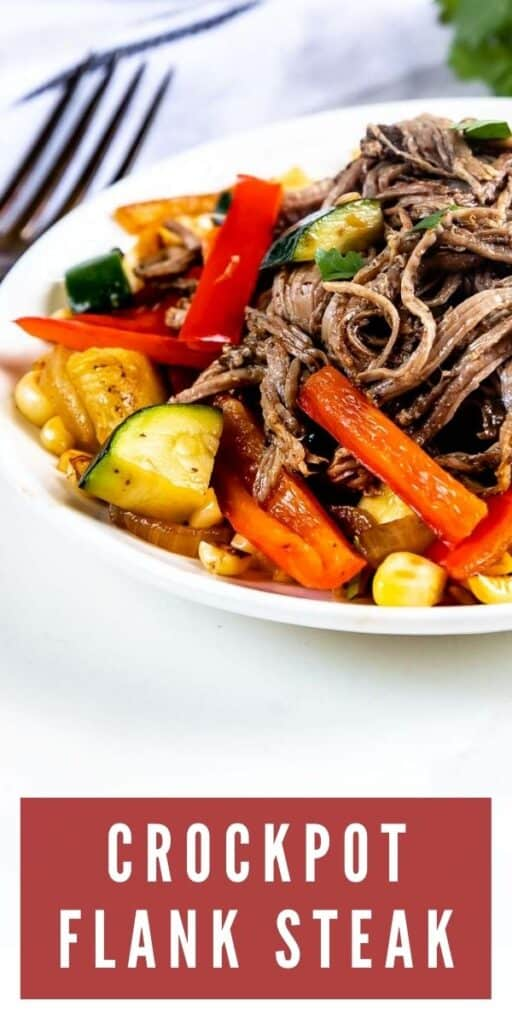 Crockpot flank steak on a plate with veggies and recipe title on bottom of image