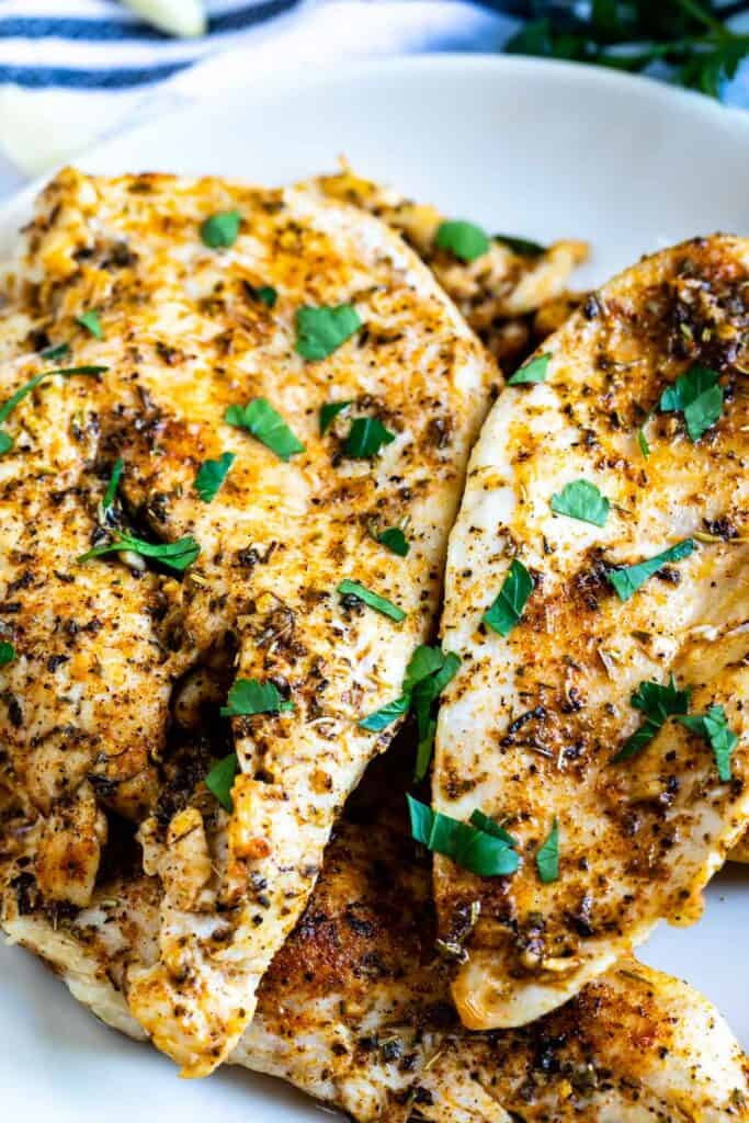 Close up shot of garlic butter chicken breasts on white plate