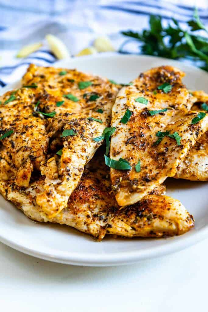 White plate full of garlic butter chicken breasts