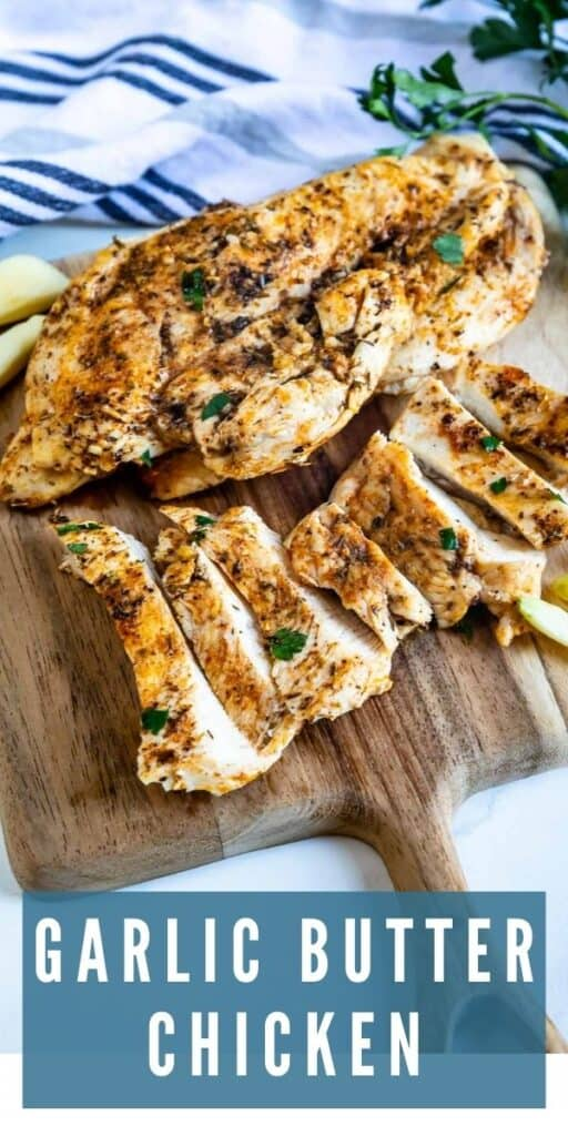 Garlic butter chicken cut into strips on a wooden cutting board with recipe title on bottom of photo