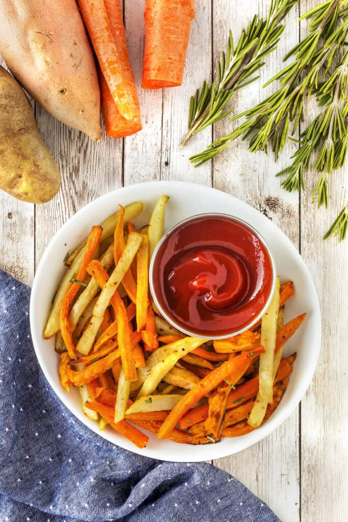Overhead shot of air fryer fries with ketchup in a white bowl