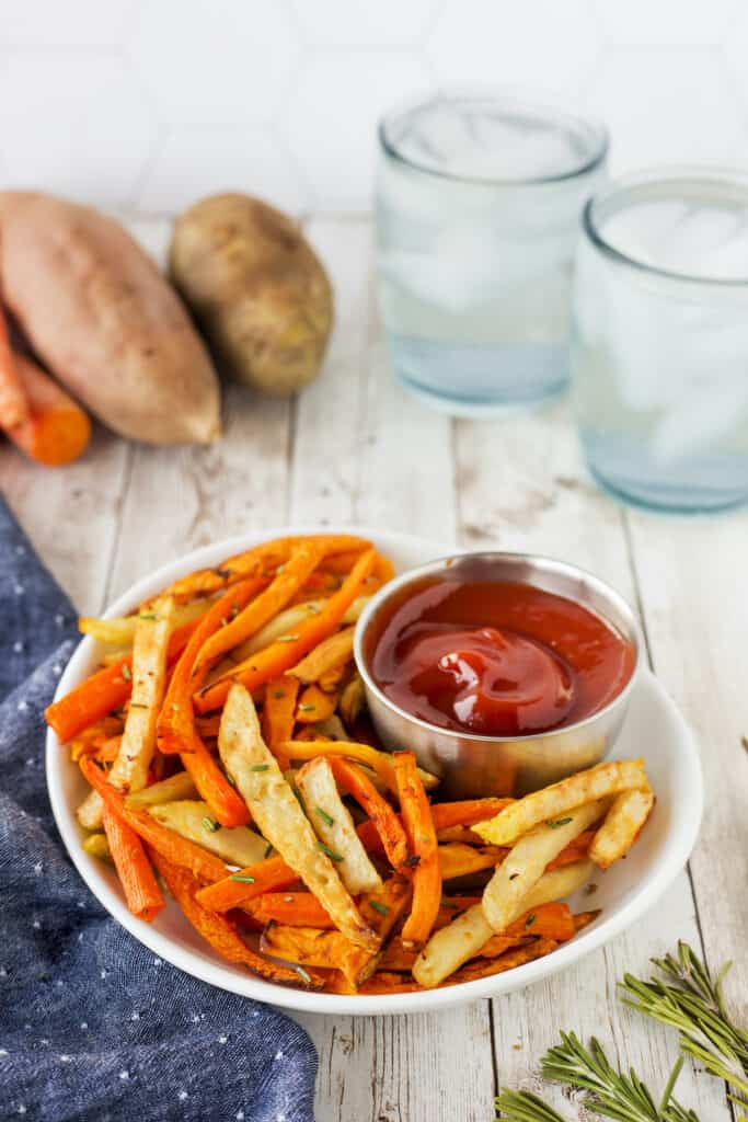 Air fryer trio rosemary fries in a white dish with ketchup and ingredients in the background