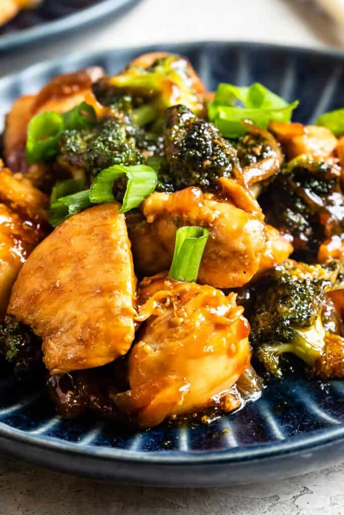 Close up shot of chicken and broccoli stir fry on plate